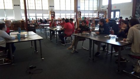Varsity Scholastic teams face off on November 28, 2018. Bayside's team is in red, on the left, and Kempsville's team is on the right. The judge and timekeeper sit in a table in front.