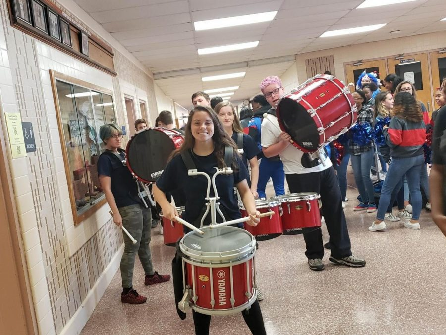 Faith+Coley%2C+sophomore+and+percussion+caption%2C+leading+the+drumline+in+a+parade+through+the+school.+