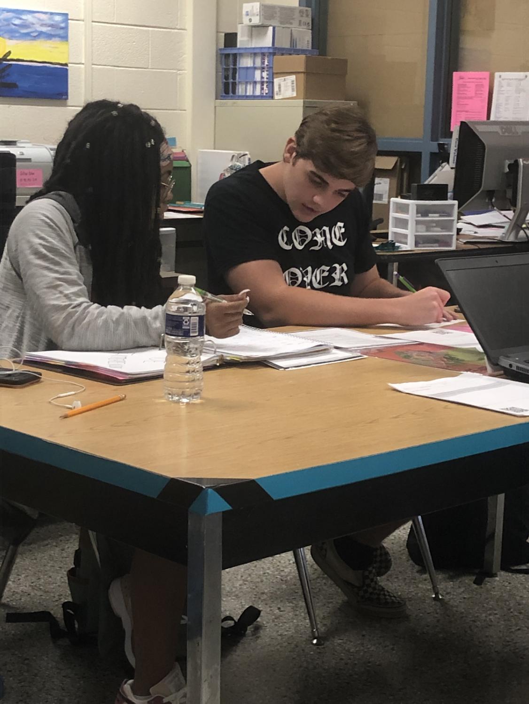 Kicking off the tutoring center, Cade Black (right) guides Dani Crumpton (left) through rigorous classwork.
