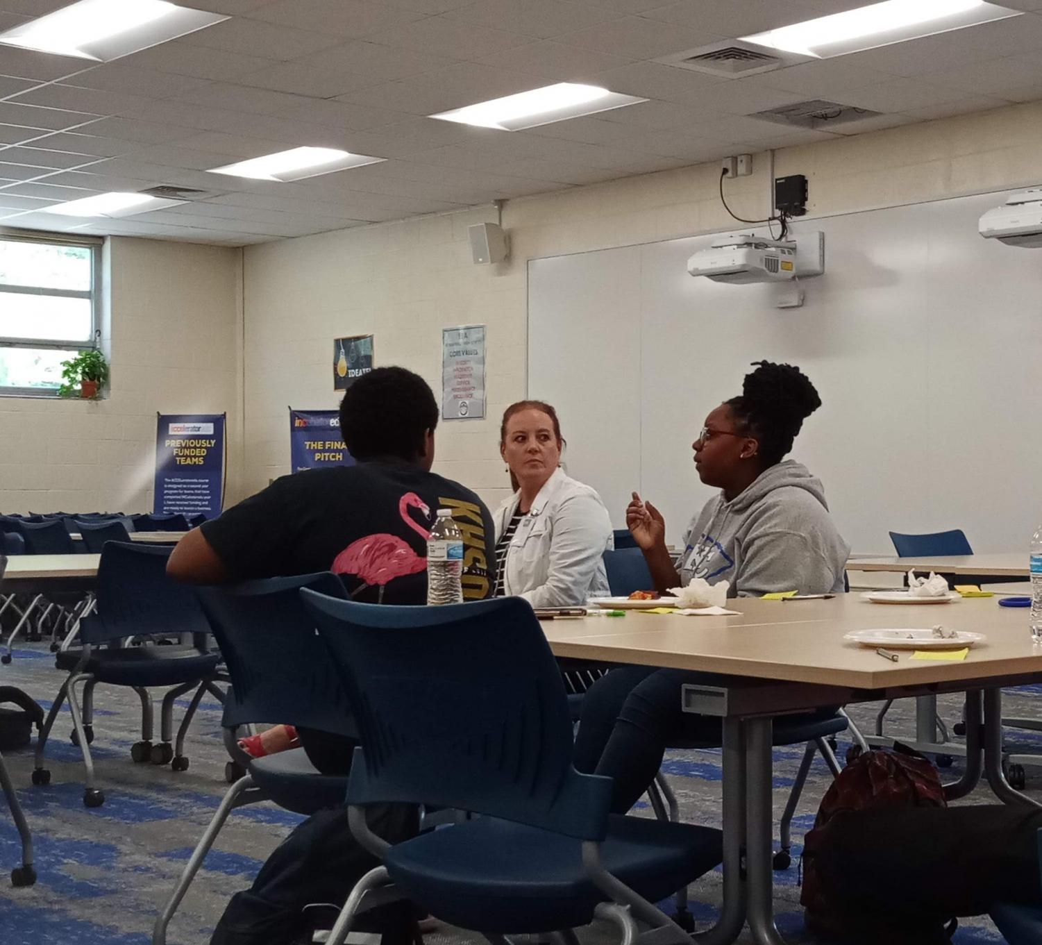 N'Kosi-Sanai Poole (left), Principal Melissa George (center), and Jada Jones (right) talk about school spirit and Monday Morning Meetings in the EBA space on October 3 during lunch.