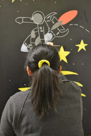 Karmina Buensuceso, senior, painting a spaceman on a rocket in the boys bathroom by the auditorium.