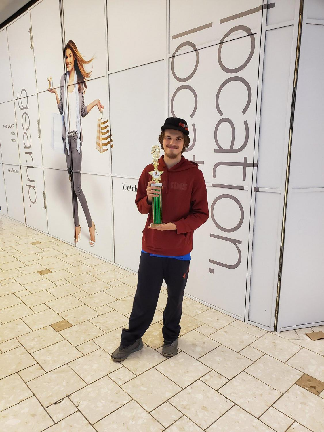 Preston Lewis, Chess Club member, with his trophy from his win at the tournament at MacArthur Mall last year.