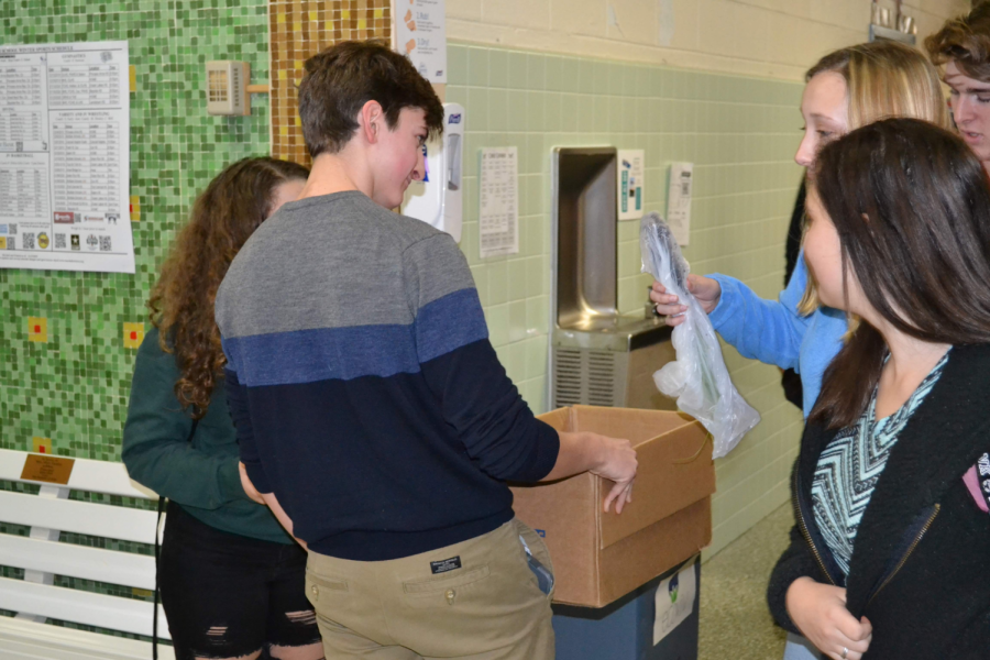 Evan Nied handing out saplings to departing Kempsville students at the end of the day on December 13 as part of his Planting Shade mission