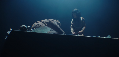 The slab descends into a purgatory-like area amidst a beam of light. Goreng, played by Iván Massagué, is collapsed on the left.. Zihara Llana, who played the girl, is on the right.